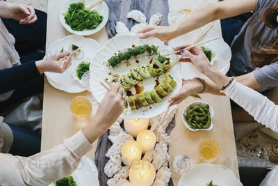 Overhead view of people sharing a celebration meal with plates of sushi.