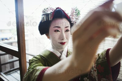 A woman in traditional geisha make up