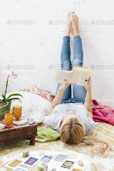 A young woman in jeans lyng on her back with her legs against the wall.