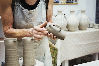 A potter handling a wet clay pot, smoothing the bottom and preparing it for kiln firing.