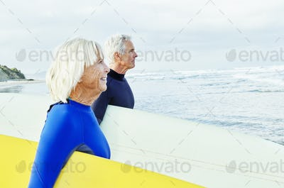 Senior woman senior man standing on a beach, wearing wetsuits and carrying surfboards.