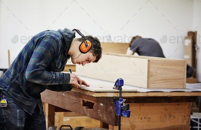 A man marking a piece of wood with a pencil.