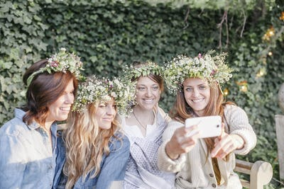 Four smiling women with flower wreaths in their hair sitting in a garden, taking a selfie.