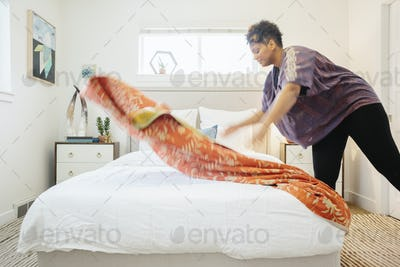 A woman spreading a floral patterned quilt across a double bed in a light airy bedroom.