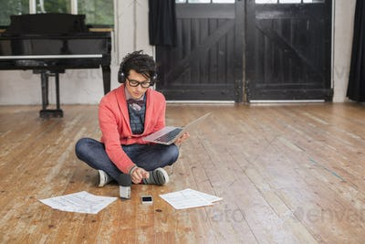Young man  in a music rehearsal studio, using a laptop computer, looking at sheet music.