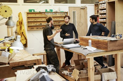 Three people in a furniture workshop, discussing a plan.