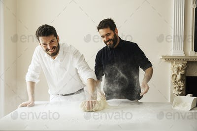 Two bakers standing at a table, kneading bread dough, dusting it with flour.