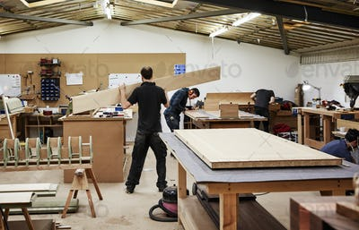 Two men working with wood in a furniture workshop.
