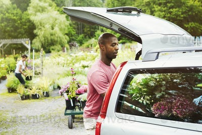 Car parked at a garden centre, man loading flowers into the boot.