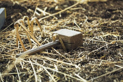 Close up of a wooden mallet lying on a bed of straw.