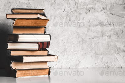 Education and reading concept, group of old colorful books on the white table on the gray background