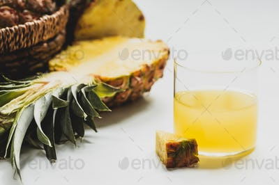 Close up View of Fresh Pineapple Juice Near Cut Delicious Fruit on White Background