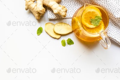 Top View of Hot Tea on Napkin Near Ginger Root, Lemon And Mint on White Background