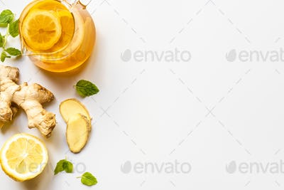 Top View of Hot Tea in Glass Teapot Near Ginger Root, Lemon And Mint on White Background