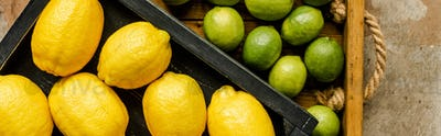 Top View of Lemons And Limes in Wooden Boxes on Weathered Surface, Panoramic Shot
