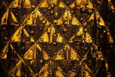 Close up View of Geometric Faceted Glass With Yellow Illumination in Dark