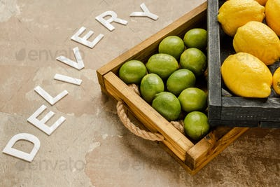 Ripe Lemons And Limes in Wooden Boxes Near Word Delivery on Weathered Surface