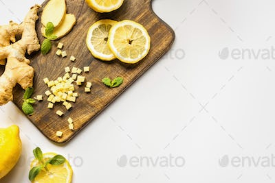 Top View of Ginger Root, Lemon And Mint on Wooden Cutting Board on White Background