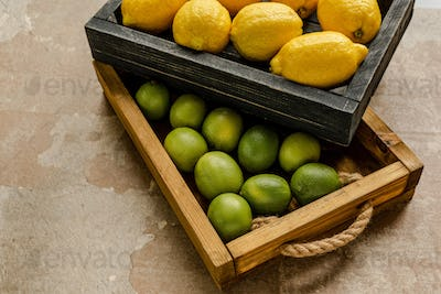 Ripe Lemons And Limes in Wooden Boxes on Weathered Surface