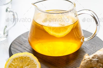 Close up View of Hot Tea in Teapot on Wooden Board Near Ginger Root, Lemon on White Background