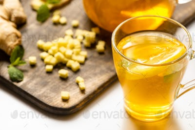 Hot Tea Near Ginger Root, Lemon And Mint on Wooden Cutting Board on White Background