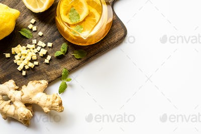 Top View of Hot Tea Near Ginger Root, Lemon And Mint on Wooden Cutting Board on White Background