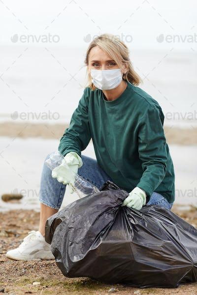Woman picking up plastic bottles