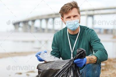 Volunteer putting garbage in bag