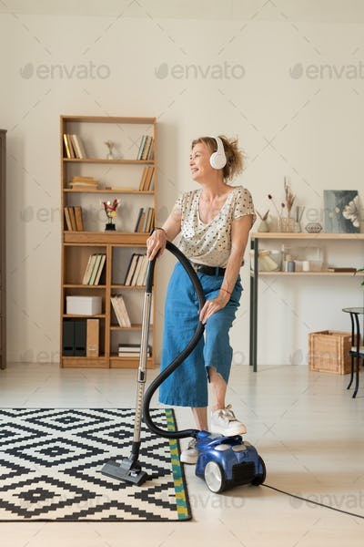 Happy mature female in homewear using vacuum cleaner while cleaning living-room