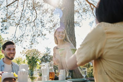 Happy young blond woman taking plastic container with salad over served table