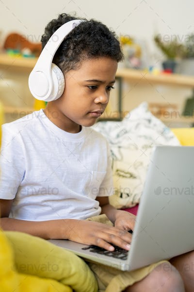 Elementary schoolboy of African ethnicity with headphones typing on laptop