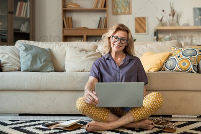 Happy mature cross-legged female holding laptop while looking at its display