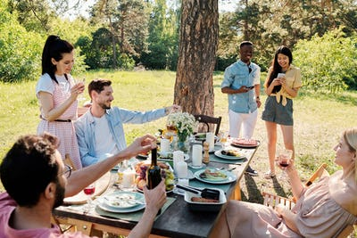 Three happy young couples in casualwear enjoying outdoor dinner on sunny day