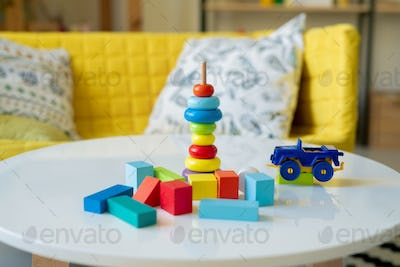 Large group of small wooden cubes of various colors and plastic lorry on table