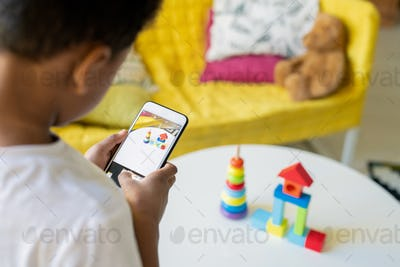 Contemporary little mixed-race boy holding smartphone over table with his toys