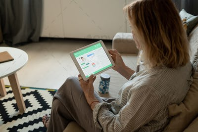 Contemporary mature woman with tablet looking through medical website