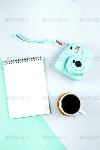 Flat lay with modern mini camera, empty notebook and cup of coffee. Fashion blogger, minimal concept