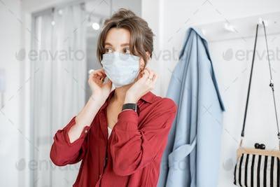 Woman wearing medical mask at home