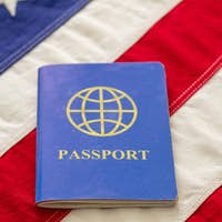 Blue passport on USA flag background, close up view.