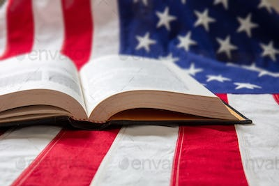 Open book on USA flag background, close up view.
