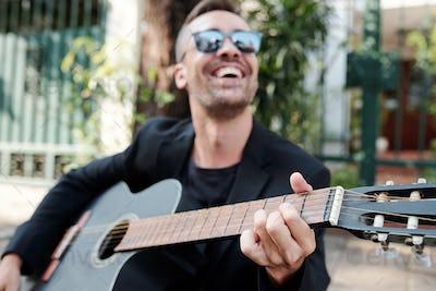 Joyful musician playing guitar