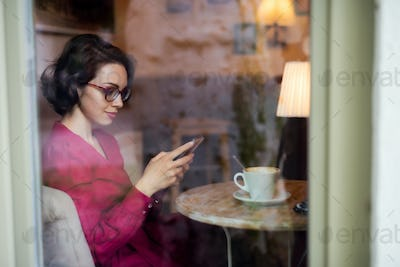 Young woman with coffee sitting indoors in cafe, using smartphone