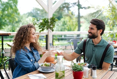 Happy couple sitting outdoors on terrace restaurant, clinking glasses