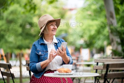 Senior woman with hat sitting outdoors in cafe, using smartphone