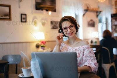 Young woman with headset and laptop indoors in cafe, working