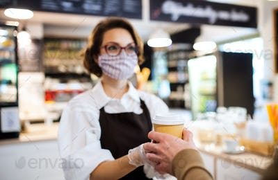 Young woman with face mask working indoors in coffee shop, serving customer