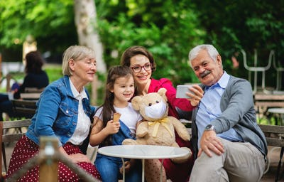 Senior couple with daughter and granddaughter sitting outdoors in cafe, taking selfie