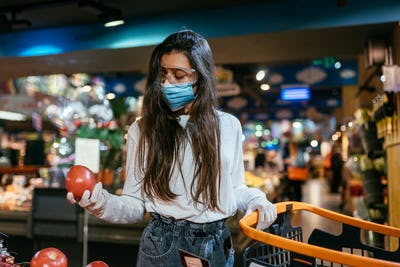 The girl with surgical mask is going to buy tomatos