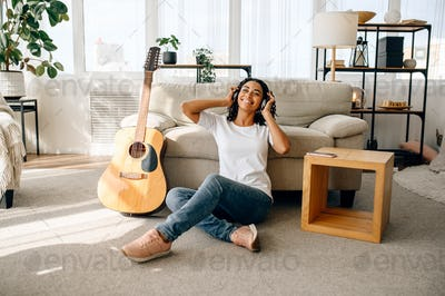 Smiling woman in headphones, guitar on background