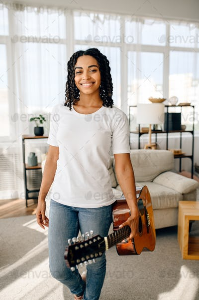 Attractive woman with guitar poses at home